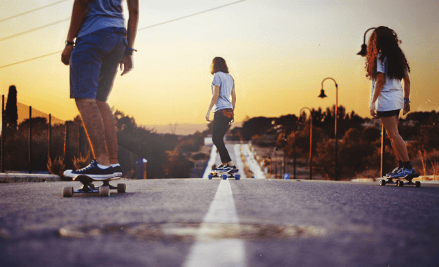 three young persons longboarding down a long road